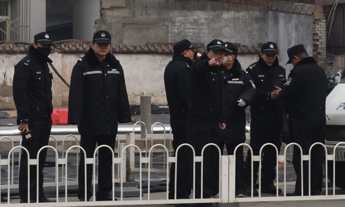 Police officers stand guard outside the No. 2 Intermediate People's Court where human rights lawyer Pu Zhiqiang was being sentenced in Beijing on Dec. 22, 2015. (Greg Baker/AFP via Getty Images)