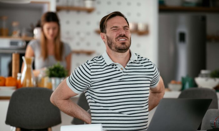 Sitting at your computer and looking down at your phone often lead to slouching and slouching takes a toll. (Just Life/Shutterstock)