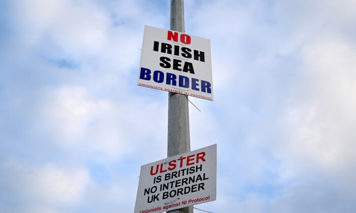 """Signs reading """"No Irish Sea border"""" and """"Ulster is British, no internal UK Border"""" are seen affixed to a lamp post at the Port of Larne, Northern Ireland, on March 6, 2021. (Clodagh Kilcoyne/Reuters)"""