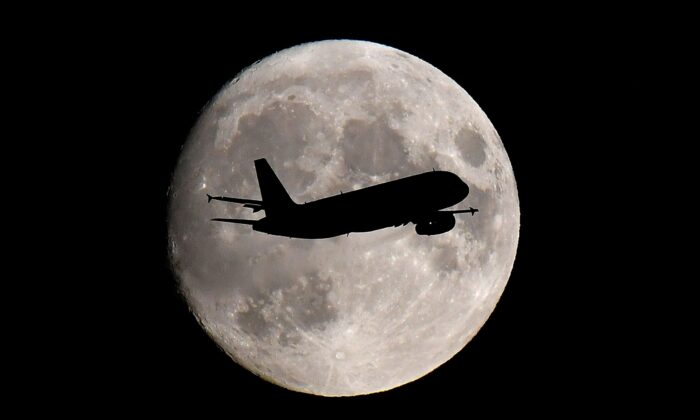 A passenger plane passes in front of the moon as it makes its final landing approach to Heathrow Airport in London, Britain, on Sept. 12, 2019. (Toby Melville/Reuters)