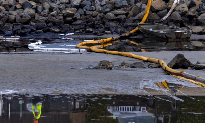 A worker is reflected in the water of an estuary after a major oil spill off the coast of California came ashore in Huntington Beach, Calif., U.S. on Oct. 4, 2021. (Mike Blake/Reuters)