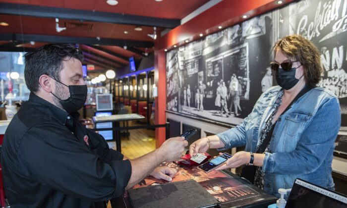 A woman's COVID-19 QR code is scanned at a restaurant in Montreal on Sept. 1, 2021. ( Canadian Press/Graham Hughes)