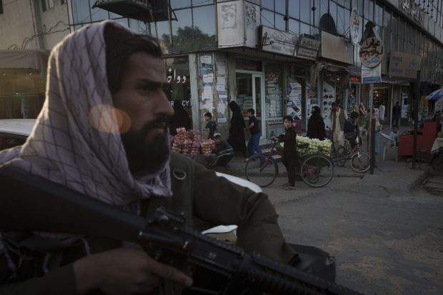 A boy looks as an Afghan fighter rides in the back of a vehicle during a police patrol in Kabul on Sept. 14. (Felipe Dana/ Associated Press)