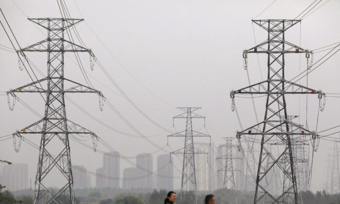 People walk past electricity pylons in Shenyang, Liaoning province, China September 29, 2021. (REUTERS/Tingshu Wang)