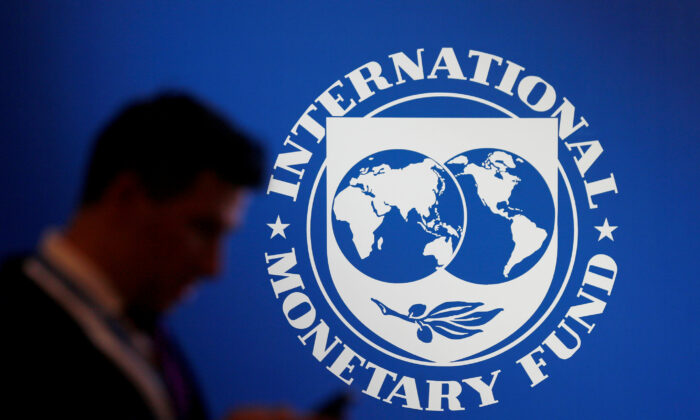 Participants are standing near the IMF logo at the International Monetary Fund / World Bank Annual Meeting on October 12, 2018 in Nusa Dua, Bali, Indonesia.  (John P. Christo / Reuters)