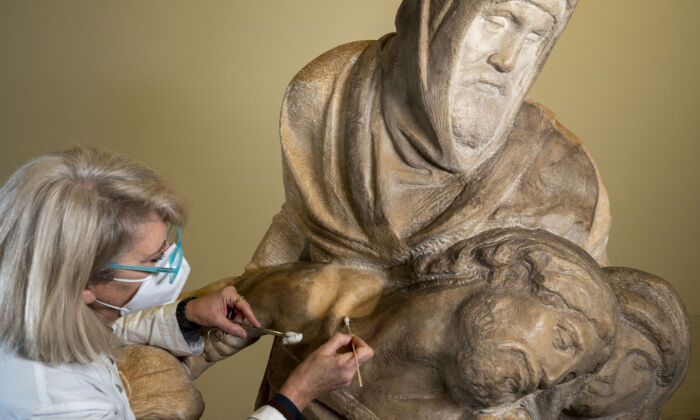A conservator carefully cleans the