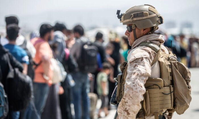 A Marine with Special Purpose Marine Air-Ground Task Force-Crisis Response-Central Command provides assistance during an evacuation at Hamid Karzai International Airport in Kabul, Afghanistan, on Aug. 22, 2021. (Sgt. Samuel Ruiz/U.S. Marine Corps via AP)