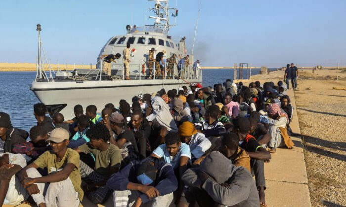 In this photo, rescued migrants looking to use the restive North African country as way to get to Europe, are seated next to a coast guard boat in the city of Khoms, Libya, on Oct. 1, 2019. (Hazem Ahmed/AP Photo)