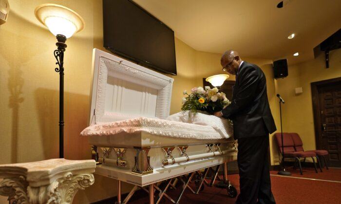 A funeral director arranges flowers on a casket before a service in Tampa, Fla., on Sept. 2, 2021. (Chris O'Meara/AP Photo)
