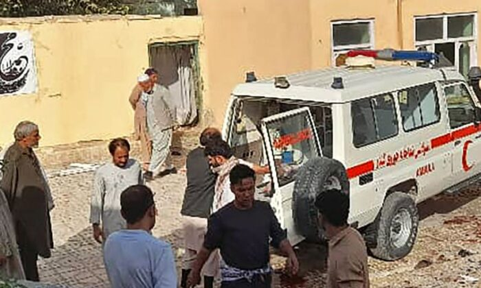 Afghan men stand next to an ambulance after a bomb attack at a mosque in Kunduz, Afghanistan, on Oct. 8, 2021. (AFP via Getty Images)