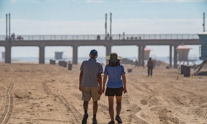 A couple walks along the beach in Huntington Beach, Calif., on Oct. 6, 2021. (John Fredricks/The Epoch Times)