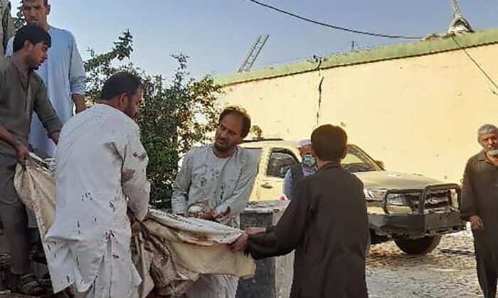 Afghan men carry the dead body of a victim to an ambulance after a bomb attack at a mosque in Kunduz on October 8, 2021. (AFP via Getty Images)