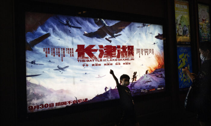 """A boy poses in front of the movie poster of """"The Battle At Lake Changjin"""" in a cinema in Wuhan, Hubei Province, China, on Oct. 2, 2021. (Getty Images)"""