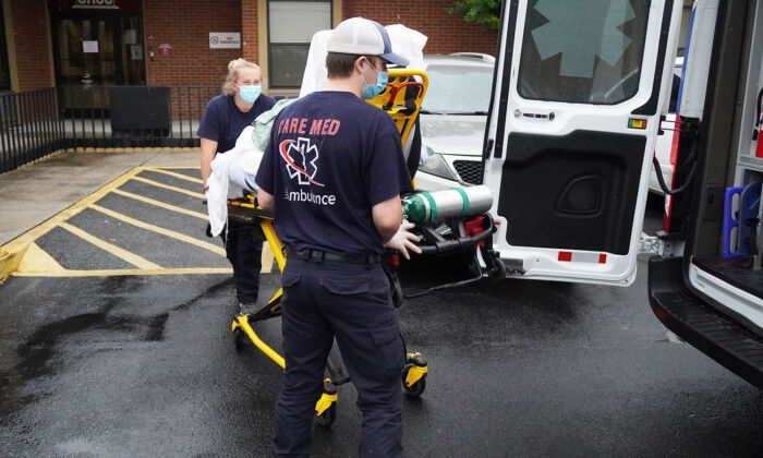 EMS workers Ethan Webber and Bailey Thornton wheel an obese patient to an ambulance in Chattanooga, Tenn., on Oct. 4, 2021. (Jackson Elliott/The Epoch Times)