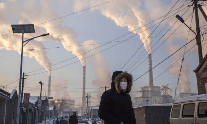 Smoke billows from stacks as a Chinese woman wears as mask while walking in a neighborhood next to a coal fired power plant in Shanxi, China, on November 26, 2015. (Kevin Frayer/Getty Images)