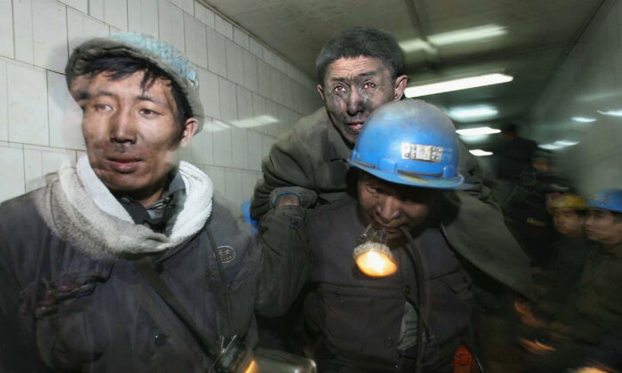 Rescuers carry a miner out after he was trapped, following a blast accident that occurred at Dongfeng Coal Mine in the suburb of Qitaihe city of Heilongjiang Province, China, on Nov. 28, 2005. (China Photos/Getty Images)
