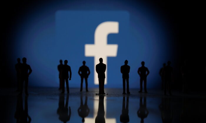 Small toy figures are seen in front of displayed Facebook logo in this illustration taken on Oct. 4, 2021. (Dado Ruvic/Reuters)