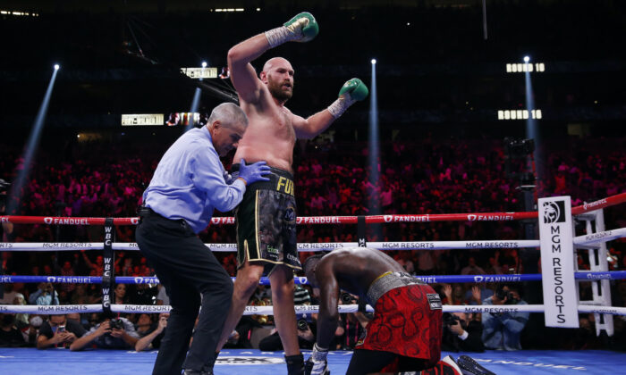 Tyson Fury, of England, knocks down Deontay Wilder in a heavyweight championship boxing match  in Las Vegas, on Oct. 9, 2021. (Chase Stevens/AP Photo)