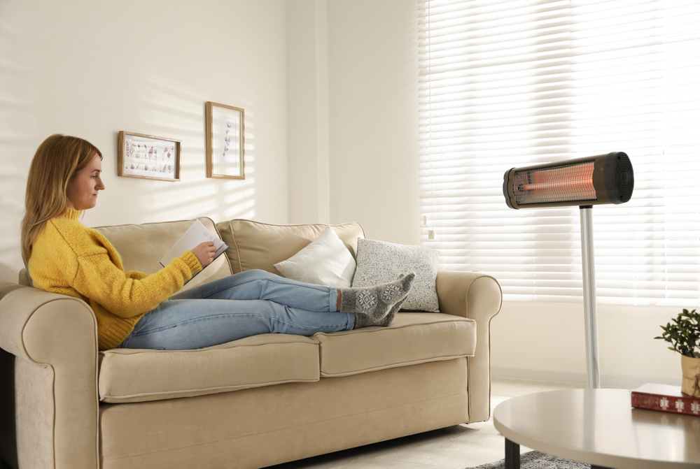 Woman,Reading,Book,Near,Electric,Infrared,Heater,In,Living,Room