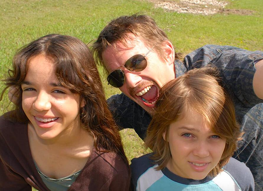 girl, man, and boy take selfie on lawn in Boyhood