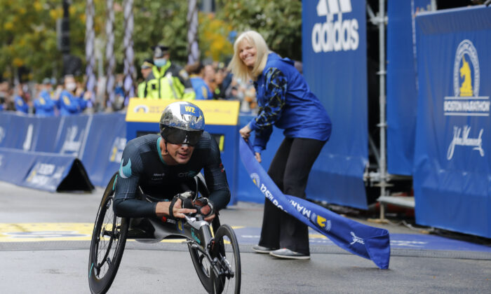 Marcel Hug, of Switzerland, crosses the finish line to win the men's wheelchair division of the 125th Boston Marathon on Oct. 11, 2021. (Winslow Townson/AP Photo)