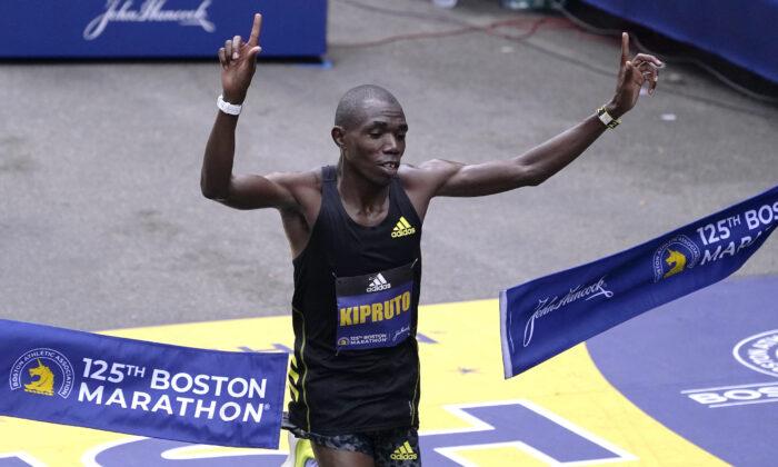 Benson Kipruto of Ethiopia breaks the finish line tape to win the Boston Marathon in Boston on Oct. 11, 2021. (Charles Krupa/AP Photo)