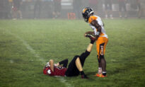 Football Mom Snaps Photo of Senior Player Helping Injured Opponent on Field—and It Goes Viral