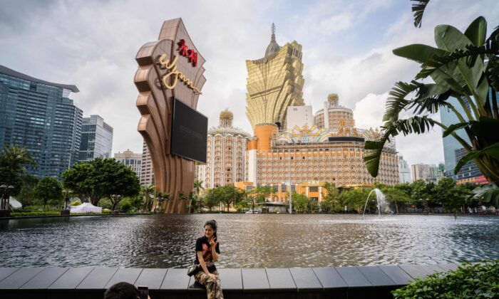 In this photo taken on March 5, 2019, visitors take photos outside the Wynn casino resort with a view of the Grand Lisboa (top C) casino resort building in Macau. (Anthony Wallace/AFP via Getty Images)