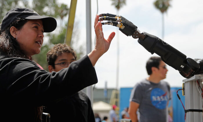 A woman reaches to touch a robotic arm developed by the Johns Hopkins University Applied Physics Laboratory on display at the Defense Advanced Research Projects Agency (DARPA, the Pentagon's science research group) Robotics Challenge Expo at the Fairplex in Pomona, California, on June 6, 2015. (Chip Somodevilla/Getty Images)