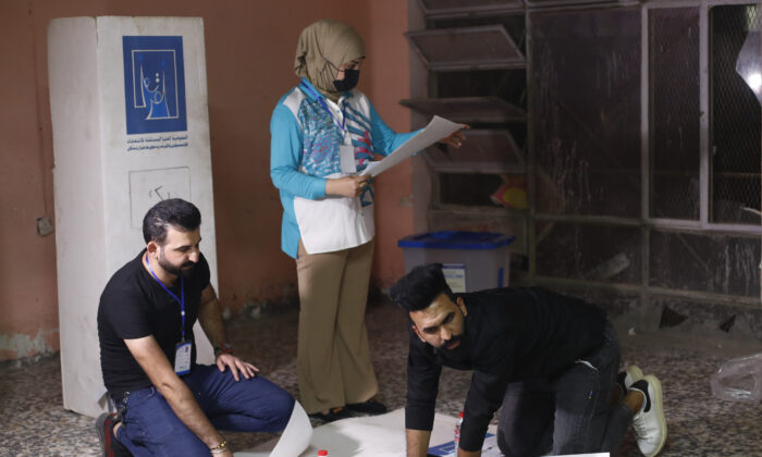 Election workers count ballots as they close a polling station at the end of voting in parliamentary elections, in Baghdad, Iraq, on Oct. 10, 2021. (Hadi Mizban/AP Photo)