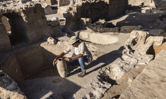 Avshalom Davidesko from the Israel's Antiquities Authority examines a jar in a massive ancient winemaking complex dating back some 1,500 years in Yavne, south of Tel Aviv, Israel, on Oct. 11, 2021. (Tsafrir Abayov/AP Photo)