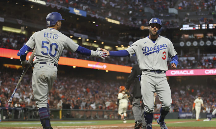 Los Angeles Dodgers' Chris Taylor (3) is congratulated by Mookie Betts (50) after scoring against the San Francisco Giants during the second inning of Game 2 of a baseball National League Division Series in San Francisco on Oct. 9, 2021. (AP Photo/John Hefti)