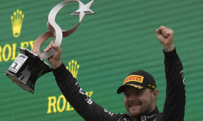 Mercedes driver Valtteri Bottas of Finland holds the trophy on the podium after winning the Turkish Formula One Grand Prix at the Intercity Istanbul Park circuit in Istanbul, Turkey, on Oct. 10, 2021. (Francisco Seco/AP Photo)