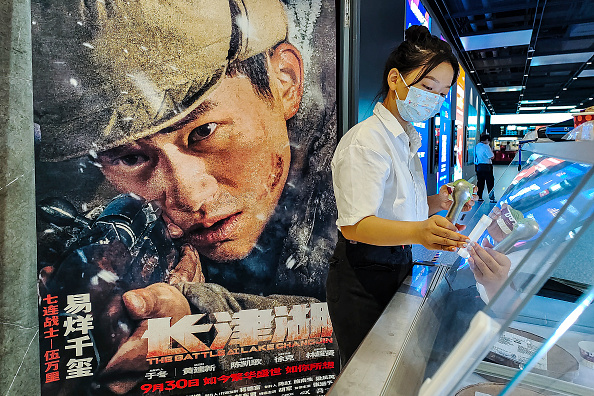 """Cinema employees sell Haagen-Dazs ice cream as the movie poster of """"The Battle at Lake Changjin"""" is seen in a cinema in Wuhan, Hubei Province, China, on Oct. 2, 2021. (Getty Images)"""