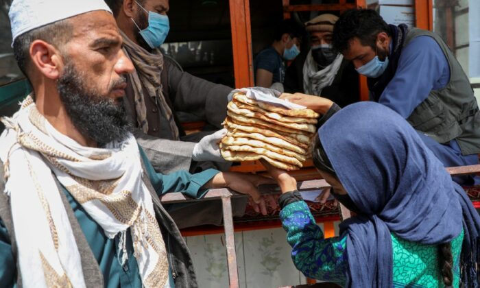 An Afghan girl receives free bread distributed by the government, outside a bakery, in Kabul, Afghanistan, on May 3, 2020. (Omar Sobhani/Reuters)