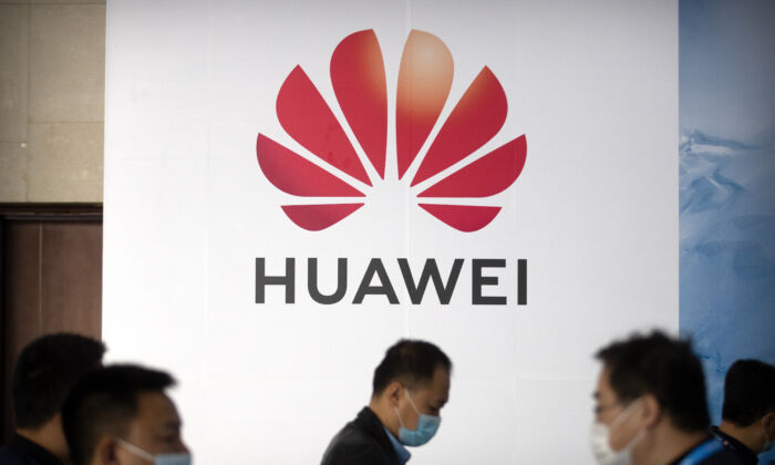 People walk past a billboard advertising Chinese tech company Huawei at the PT Expo in Beijing on Oct. 14, 2020. (AP Photo/Mark Schiefelbein)