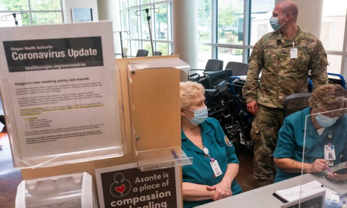 An Oregon National Guardsman works with hospital staff at an intake station at Three Rivers Asante Medical Center in Grants Pass, Oregon, on Sept. 9, 2021. (Nathan Howard/Getty Images)