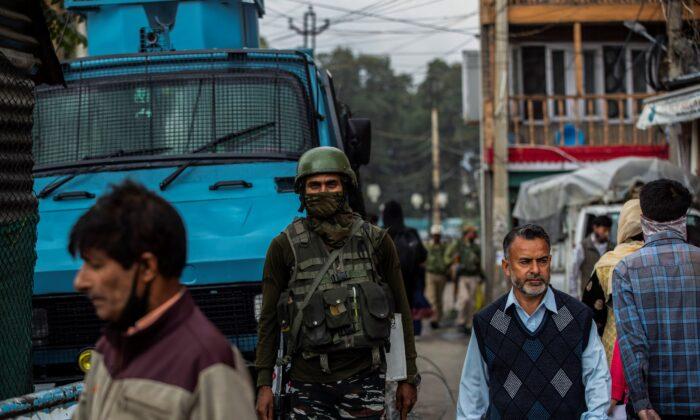 An Indian paramilitary soldier guards as a Kashmiris walk at a busy market in Srinagar, Kashmir, on Oct. 11, 2021. (Mukhtar Khan/AP Photo)