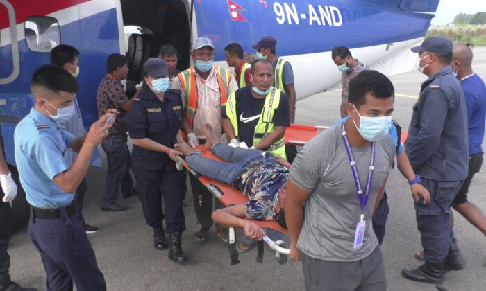 One among many passengers injured in a bus accident in western Nepal's Mugu district is rushed for treatment after being airlifted to Nepalgunj, Nepal, on Oct.12, 2021. (Krishna Adhikari/AP Photo)