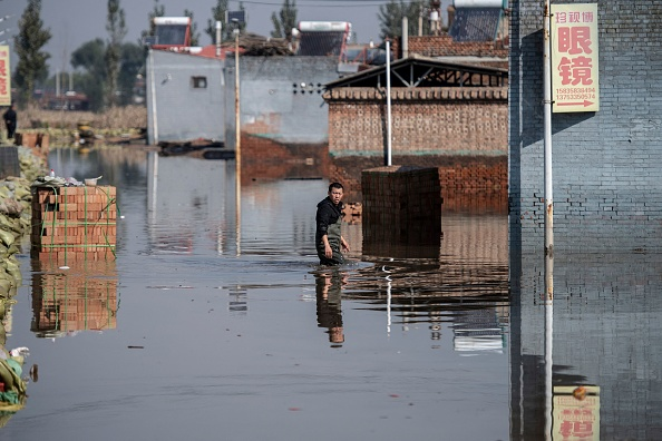 A man makes his way along a flooded area after heavy rainfall in Jiexiu in the city of Jinzhong in China's northern Shanxi Province on October 11, 2021. (China OUT/AFP via Getty Images)