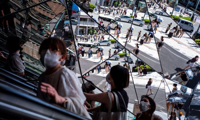 People wearing protective masks are reflected in the mirror at a shopping mall in Tokyo amid the coronavirus disease outbreak in Tokyo, Japan on Aug. 19, 2021. (Athit Perawongmetha/Reuters)