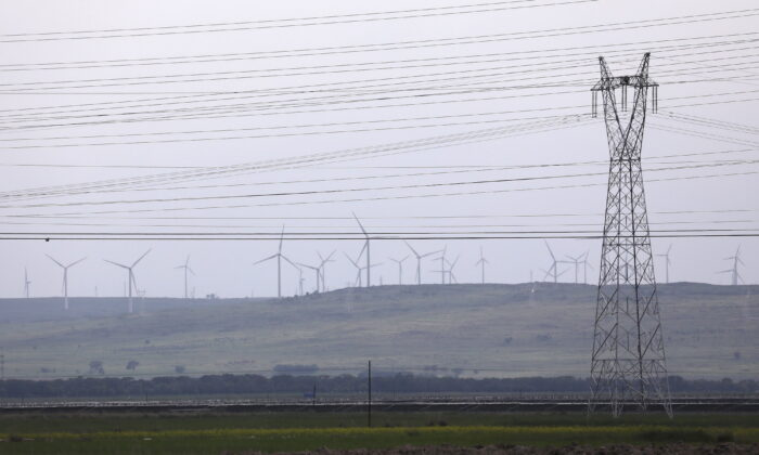 An electricity pylon and power lines are seen against a backdrop of wind turbines in Zhangjiakou, Hebei province, China, on July 15, 2021. (Tingshu Wang/Reuters)