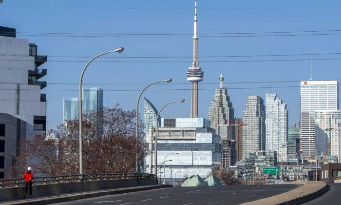 A lone runner on an empty street in Toronto during rush hour on the first working day of the new Ontario COVID-19 lockdown, on April 5, 2021. ( Canadian Press/Frank Gunn)