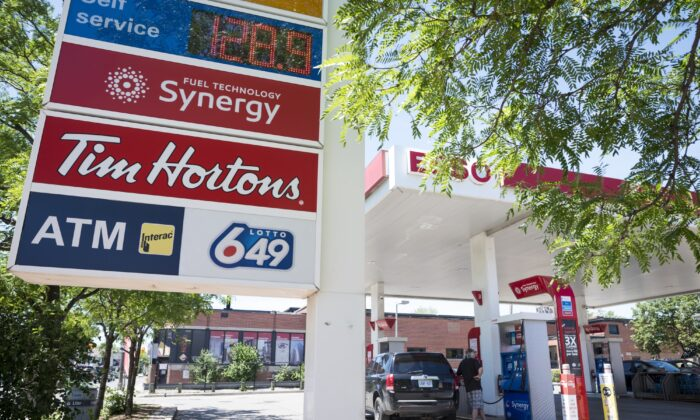 A commuter pumps gas at an Esso gas station in Toronto on June 15, 2021. As the price of oil rises, the cost of many goods in the economy are also going up. (The Canadian Press/Tijana Martin)
