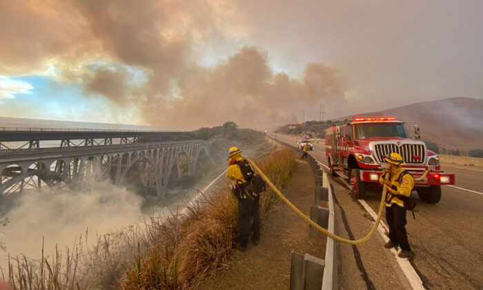 Firefighters extinguish flames that were spotted ahead of the fire front along Highway 101 southbound at Vista Point, north of Refugio State Beach in Santa Barbara County, Calif.,  on Oct. 12, 2021. (Mike Eliason/Santa Barbara County Fire Department via AP)