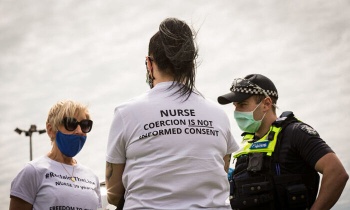 A member of Victoria Police questions a woman at Campbellfield Plaza in Melbourne, Australia, on Oct. 9, 2021. (Darrian Traynor/Getty Images)