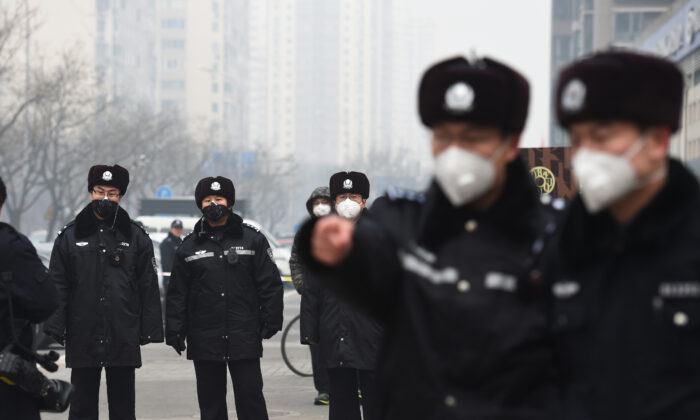 Police wear masks as they stand guard outside the No. 2 Intermediate People's Court where human rights lawyer Pu Zhiqiang was being sentenced in Beijing on Dec. 22, 2015. (Greg Baker/AFP via Getty Images)