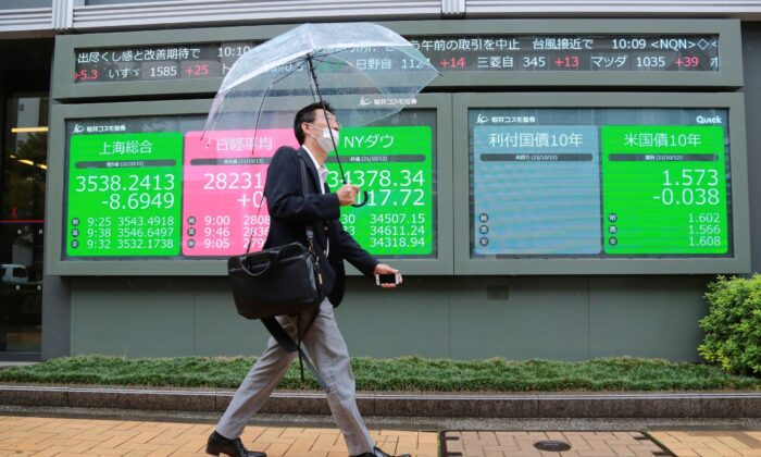A man walks by an electronic stock board of a securities firm in Tokyo, Japan on Oct. 13, 2021. (Koji Sasahara/AP Photo)