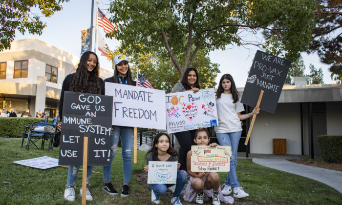 Students of PYLU School District hold up signs as parents gather to express their concerns over vaccine mandates for students at the Placentia Yorba Linda Unified School District building in Placentia, Calif., on Oct. 12, 2021. (John Fredricks/  Pezou)