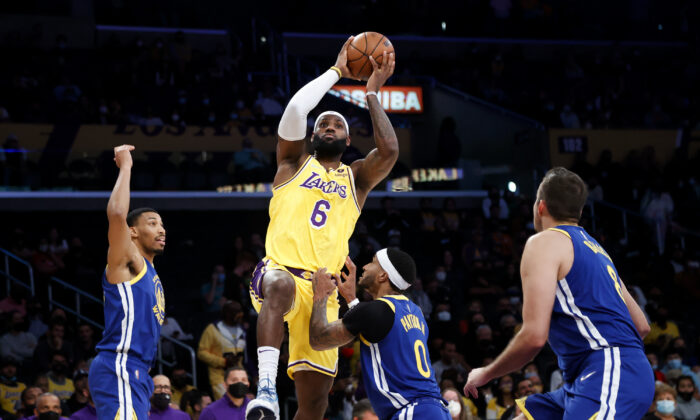 Los Angeles Lakers forward LeBron James shoots over Golden State Warriors guard Gary Payton II, second from right, during the first half of a preseason NBA basketball game in Los Angeles on Oct. 12, 2021. (AP Photo/Ringo H.W. Chiu)